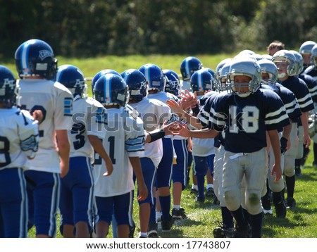Young American football teams displaying sportsmanship at the end of the game. - stock photo