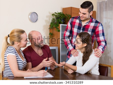 Young american spouses sitting with documents and asking friends for advice