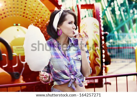 Young American Woman in Amusement Park Eating Cotton Candy
