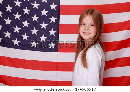 Young American woman with a beautiful smile is on the background of the American flag