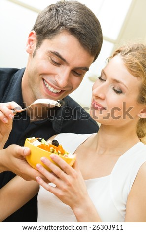 Young amorous couple eating vegetable salad together at home