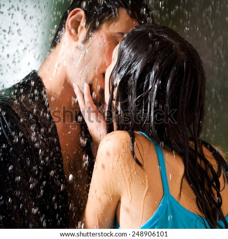 Young amorous couple hugging and kissing under a rain, outdoors