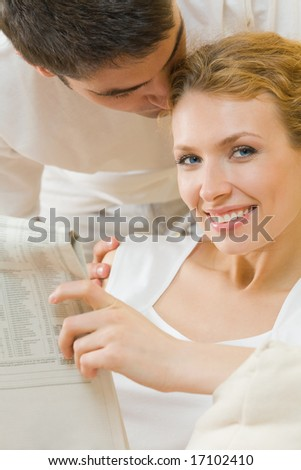 Young amorous couple reading newspaper at home - stock photo