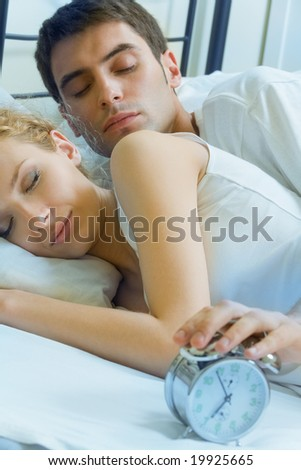 Young amorous couple waking up at the morning - stock photo