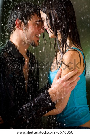 Young amorous happy couple embracing at summer rain
