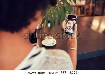 Young an and woman talking to each other through a video call on a smartphone. Young woman having a videochat with man on mobile phone. Woman sitting at a coffee shop. - stock photo