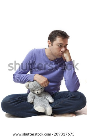 Young an thinking away while holding a toy bear