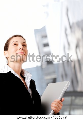 Young and ambitious businesswoman looks at the future in front of an office building. - stock photo