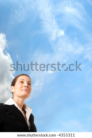 Young and ambitious businesswoman looks at the future in front of the blue sky. - stock photo