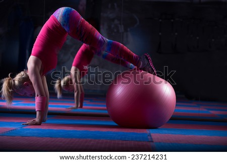 Young and athletic girl using fitness ball in a gym. Fitness ball at gym workout fitness and pilates exercise.Young woman doing some pilates exercises with a ball - stock photo