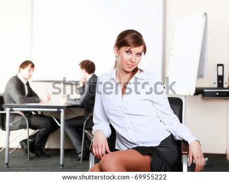 young and attractive businesswoman in an office with collegues on the background