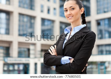 young and attractive businesswoman in suit , image is taken outdoors on a street - stock photo