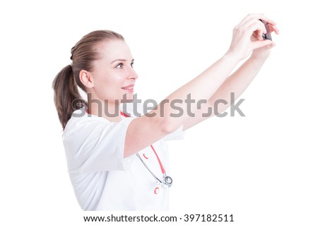 Young and attractive female doctor or medic taking a selfie using phone camera isolated on white background - stock photo