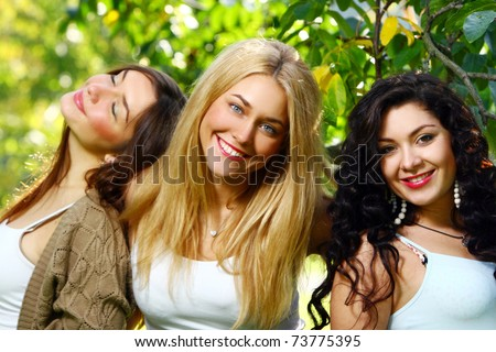 Young and attractive girlfriends posing and have fun in park - stock photo