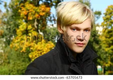 Young and attractive guy posing in park beside a tree - stock photo