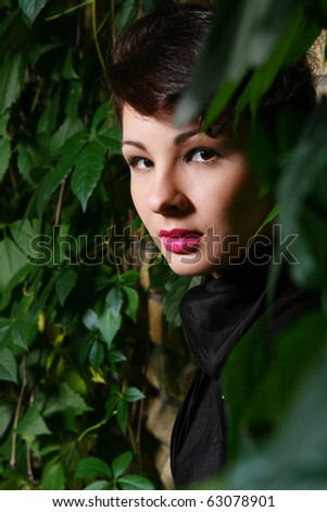 Young and attractive lady beside with brick wall, overgrown of vine leaves
