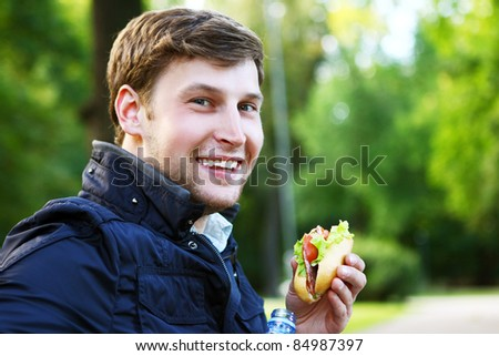Young and attractive man relaxes in the park at lunch time - stock photo