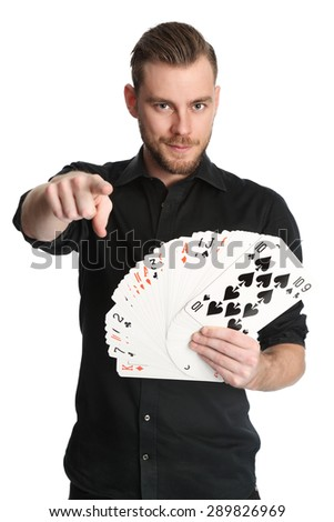 Young and attractive man wearing a black shirt with his sleeves rolled up, holding a fan of big sized cards. White background.