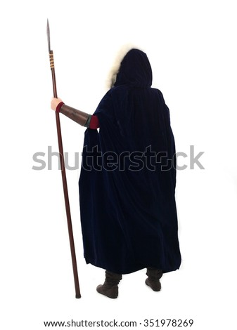 young and attractive red haired  female warrior,  wearing a red medieval tunic and leather Armour, velvet fur lined cloak. holding a spear as a weapon. back view. isolated on a white background. - stock photo