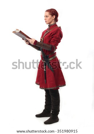 young and attractive red haired  female warrior,  wearing a red medieval tunic and leather Armour. holding magical book. isolated on a white  - stock photo