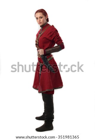 young and attractive red haired  female warrior,  wearing a red medieval tunic and leather Armour.  isolated on a white - stock photo