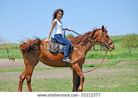 young and attractive woman riding brown horse