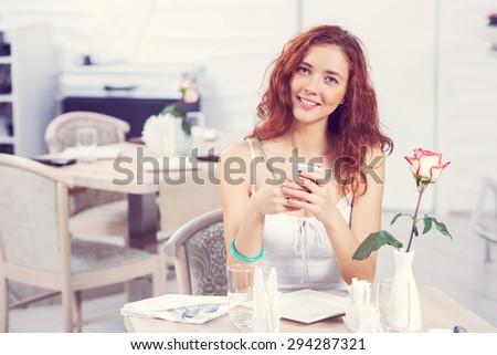 Young and attractive woman sitting in cafe and using cellphone - stock photo