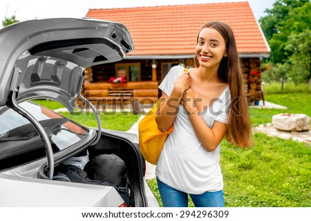 Young and attractive woman with yellow back standing near the car with wooden house on background. Countryside vacations concept - stock photo