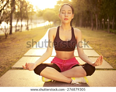 young and beautiful asian woman practicing yoga outdoors in park in warm sunlight, meditation, fitness, healthy life and lifestyle concept. - stock photo