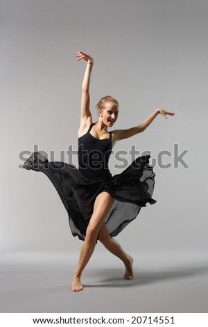 young and beautiful ballerina posing on grey background - stock photo