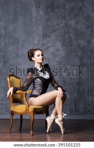 Young and beautiful ballerina with a perfect body sitting on a retro armchair.  - stock photo