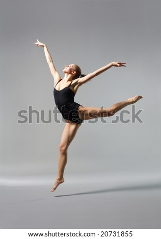 young and beautiful ballet dancer posing on gery - stock photo