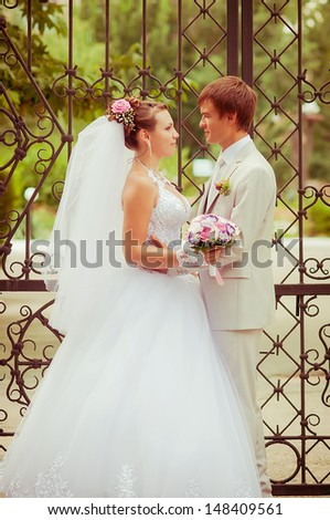 young and beautiful bride and groom smiling at each other - stock photo