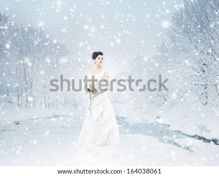 Young and beautiful bride with the flower bouquet in winter forest - stock photo