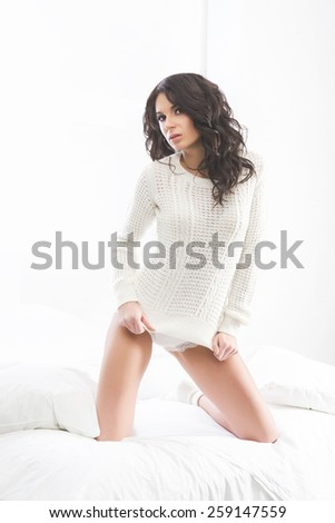 Young and beautiful brunette woman posing in the bed. Morning light from the window.