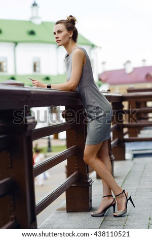 Young and beautiful business woman the street in the summer city. In the hands of smart watches. - stock photo