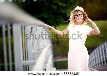 Young and beautiful cheerful girl in a hat and glasses walking in summer city and smiles - stock photo