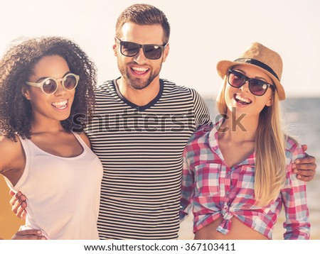 Young and beautiful. Cheerful young man embracing two women while standing at the seaside together - stock photo