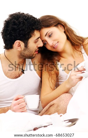 Young and beautiful couple having breakfast in bed - stock photo