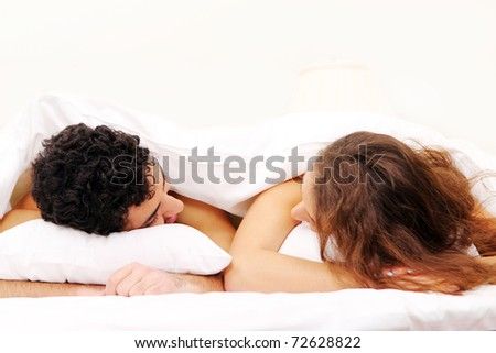 Young and beautiful couple in bed - stock photo