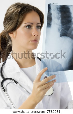 young and beautiful doctor looking at x-ray - stock photo