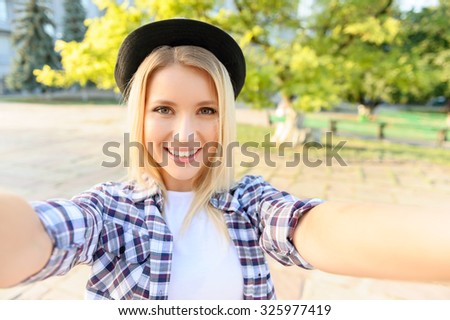 Young and beautiful. Elated pretty girl making selfie while having a walk around the city - stock photo