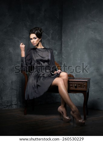 Young and beautiful fashion model over vintage and shabby background - stock photo