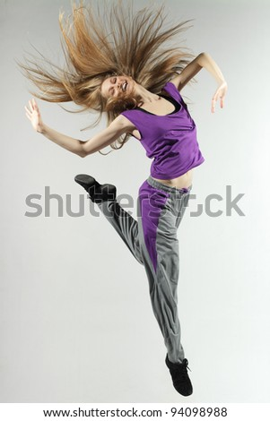 Young and beautiful female jumping high over grey background - stock photo