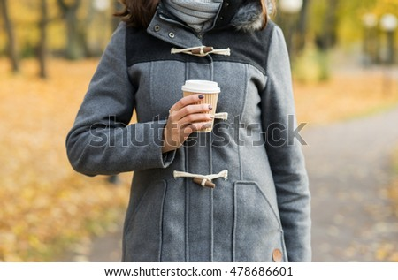Young and beautiful girl drinking coffee in bright and colorful autumn park