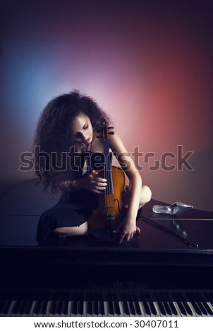Young and beautiful girl playing on grand piano - stock photo