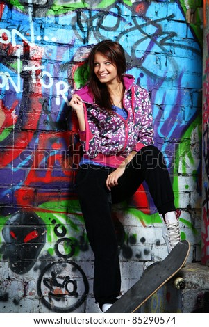 Young and beautiful girl posing against wall with graffiti
