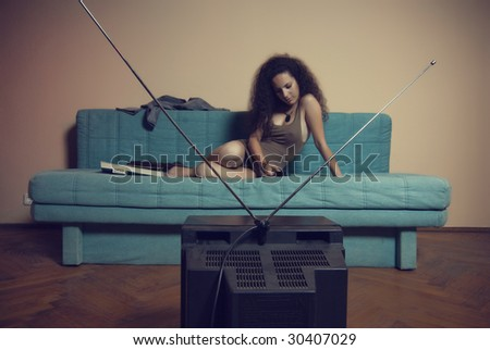 Young and beautiful girl resting and watching to a tv on a sofa - stock photo