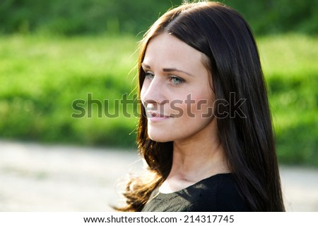 Young and beautiful lady is smiling and enjoying her time in nature - stock photo