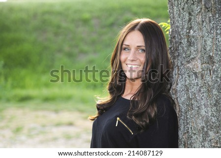 Young and beautiful lady is smiling and enjoying her time in nature by the tree - stock photo